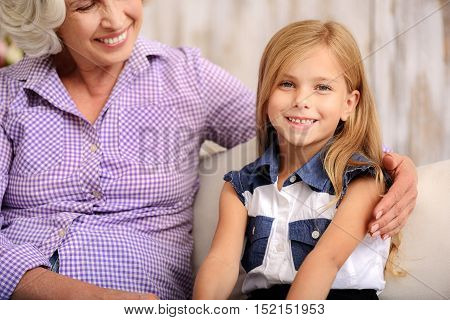 Pretty girl is visiting her grandmother. She is looking at camera and laughing. Mature woman is sitting on sofa and hugging her grandchild with love