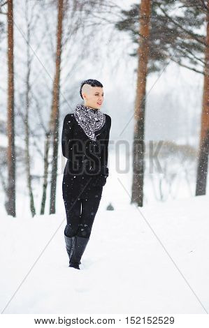 Full length winter portrait of beautiful happy woman in at wintry park.