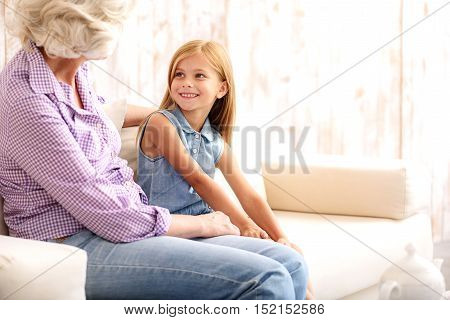 Happy little girl is spending time with her grandmother. She is looking at old woman and smiling. Family is sitting on sofa and embracing