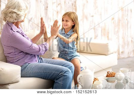 Joyful grandmother is playing with her granddaughter. They are joining palms and smiling. Family is sitting on couch at home