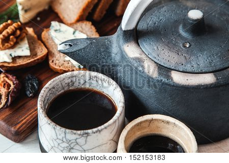 Old Ceramic Kettle With Two Cups Of Tea And Sandwiches On A Wooden Background