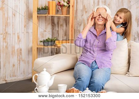 Guess who it is. Joyful girl is covering her grandmother eyes secretly. Mature woman is sitting on couch and smiling