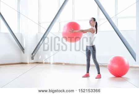 Doing a physical exercise. Happy beautiful young woman holding a ball in front of her and smiling while training