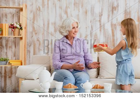 This present is for you. Pretty girl is giving a colored box to her grandmother. Old woman is sitting on sofa and smiling happy
