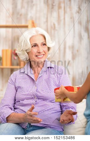 Pretty child is giving present to her grandmother. Mature woman is sitting on couch and laughing with surprise