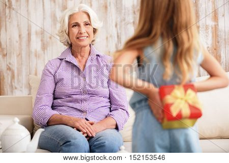 Cute little girl is standing and hiding gift box behind her back secretly. Her grandmother is sitting on sofa and looking at her with anticipation. She is smiling happily