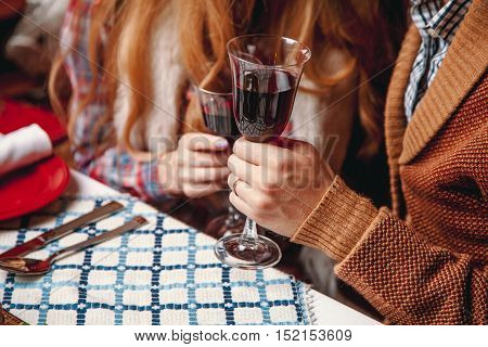 Beautiful Couple Sitting At The Laid Table For Thanksgiving Day, Holding Glass Of Wine In The Hands