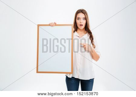 Portrait of a smiling woman pointing finger on blank board isolated on a white background