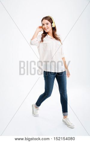 Full length of cheerful young woman listening to music from mobile phone over white background