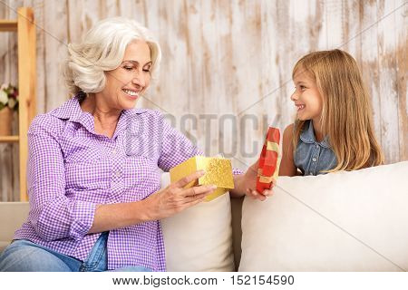 Joyful old woman is opening gift box from her granddaughter with interest. She is sitting on couch and smiling