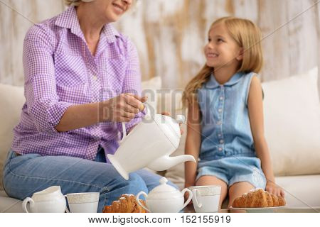 Joyful old woman is treating her granddaughter with tea. She is pouring drink into cup and smiling. Small girl is sitting on couch and looking at granny with anticipation