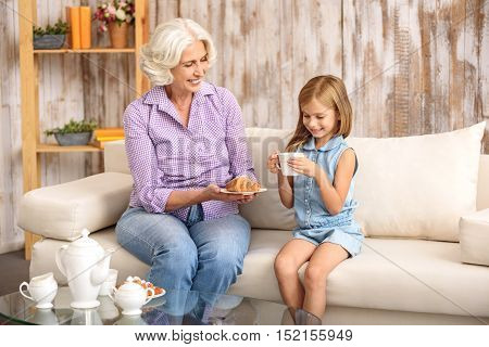 Joyful old grandmother is treating small girl with sweet breakfast. She is sitting on sofa and giving her a croissant. Child is drinking tea and smiling