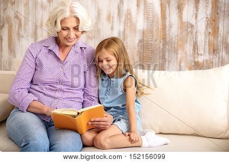 Happy grandmother is reading for her granddaughter. They are sitting on couch and smiling
