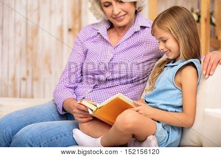 Joyful girl is reading book with her grandmother. They are sitting on sofa at home. Old woman and child are smiling