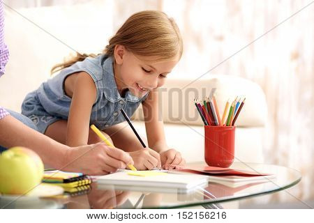 Happy little girl is drawing with aspiration and laughing. Her grandmother is helping her