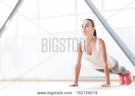 Intensive workout. Good looking determined well built woman doing push ups and concentrating on the activity while working out