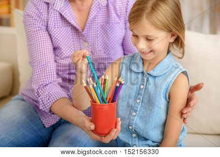 Pretty little girl is taking pencil from mug with aspiration. She is smiling. Her grandmother is sitting and embracing her with love