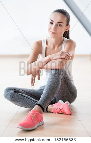 Need to rest. Joyful positive nice woman sitting on the floor and smiling while having a break