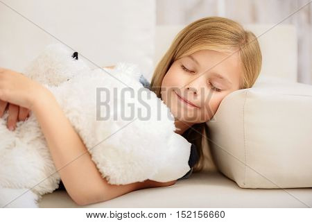 Cute girl is napping with teddy on couch innocently