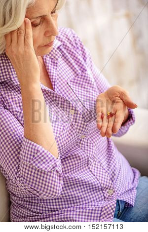 Frustrated old woman is taking pills from headache