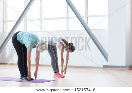 You need to reach the floor. Hard working well built slender woman standing together and bending forward while trying to reach the floor with their hands