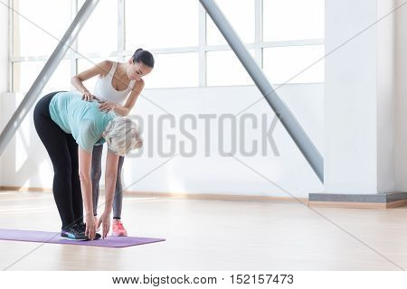 Bending exercises. Beautiful experienced fitness coach standing near the woman and looking at her while working out in a gym