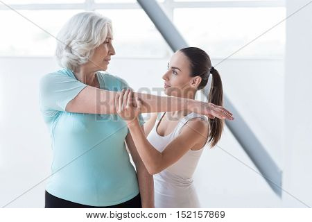 At the fitness centre. Skillful experienced female coach standing near the woman and holding her hand while looking at her