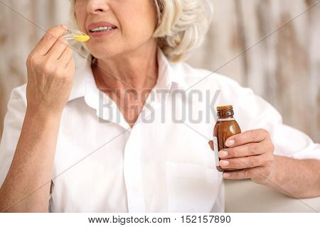 Concerned mature woman is drinking medication against illness