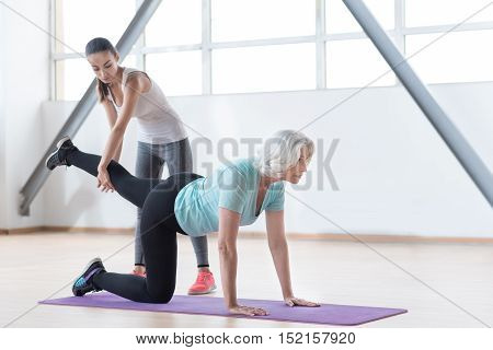 Intensive training. Thoughtful serious old woman looking forwards and holding up her leg while lying on a yoga mat