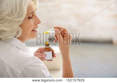 Positively motivated old woman is curing herself by cough syrup. She is sitting and smiling