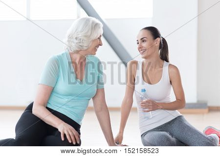 Pleasurable relaxation. Good looking optimistic slim women sitting together on the floor and looking at each other while resting during a fitness workout