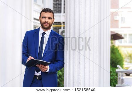 manager standing in front of a building with tablet and copy space