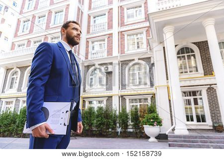 low angle view of a successful realtor with a tablet against buildings