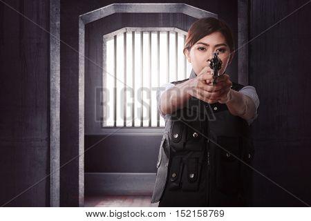 Beautiful asian woman with gun standing alone on dark room