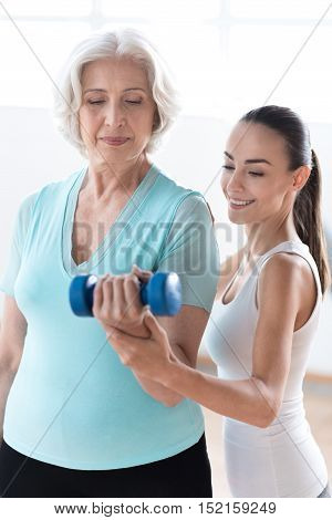 Focused on the task. Hard working persistent serious woman holding a blue dumbbell and looking at it while working out with the fitness coach