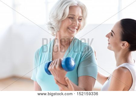 Build up your body. Joyful good looking grey haired woman holding a blue dumbbell and smiling while looking at her coach