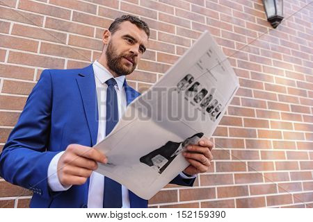 man in costume reading news outdoors, low angle