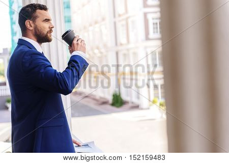 man drinking coffee outdoors and looking into the distance