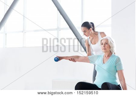 Concentrated on a physical activity. Nice pleasant hard working woman stretching out her hand and holding a dumbbell while having a workout in a fitness club