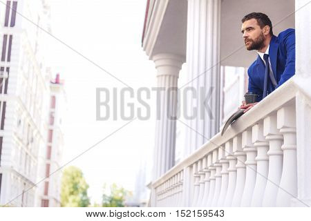 handsome man standing on a terrace of an old luxury building and looking away