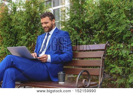freelancer sitting on a bench with laptop and cup of coffee