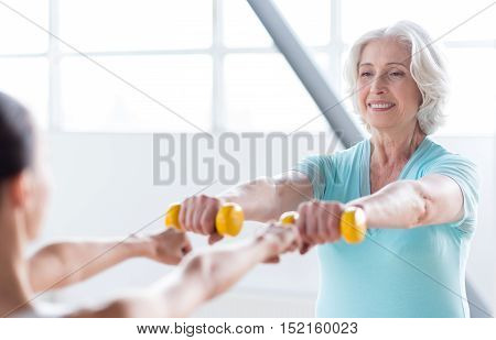 Wish to be slim. Happy good looking athletic woman holding dumbbells in front of her and looking at her coach while having a fitness class