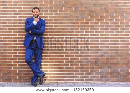 full length of a businessman in a costume standing with crossed legs against a brick wall background with copy space