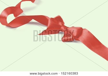 Red satin gift bow isolated on white background.