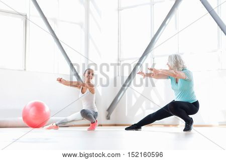 We enjoy aerobics. Happy persistent good looking women holding their arms in front of them and looking at each other while taking pleasure in their aerobics classes