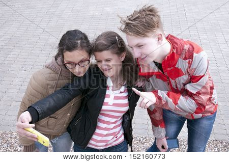 Girls and a guy doing selfie phone