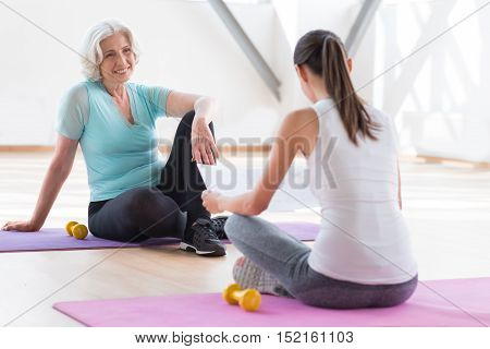 Enjoying their rest. Positive happy good looking woman sitting on a yoga mat and smiling while looking at the her coach