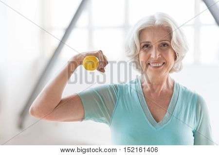 Healthy lifestyle. Delighted good looking enthusiastic woman holding a small yellow rubber dumbbell and smiling while looking at you