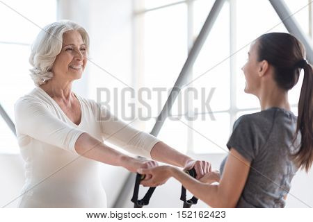 Enjoying sports activities. Pleasant active joyful woman standing opposite her coach and smiling while having a fitness workout