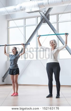 Using gymnastic sticks. Active hard working energetic women standing on the floor and holding gymnastic sticks up while focusing on the activity